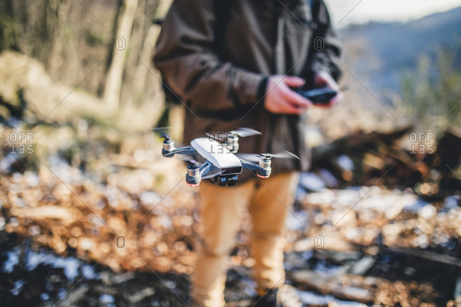 Midsection of hiker flying quadcopter in forest