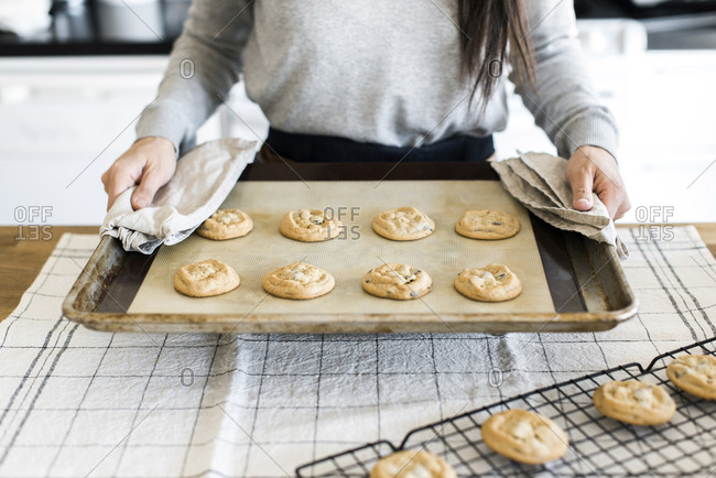 Midsection of woman holding cookies baking sheet over table in kitchen
