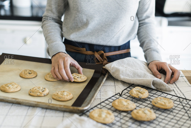Midsection of woman arranging cookies on cooling rack in kitchen
