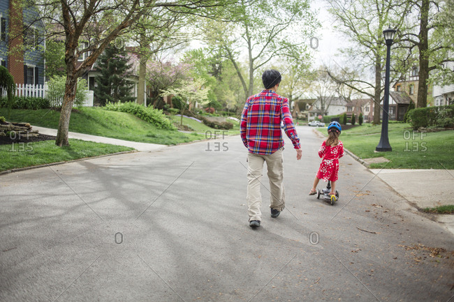Rear view of father walking by daughter riding push scooter on road
