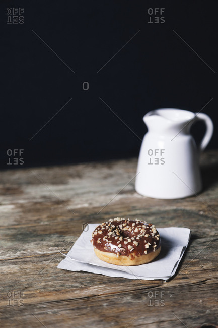 Chocolate donut with wax paper and drink on wooden table against black background