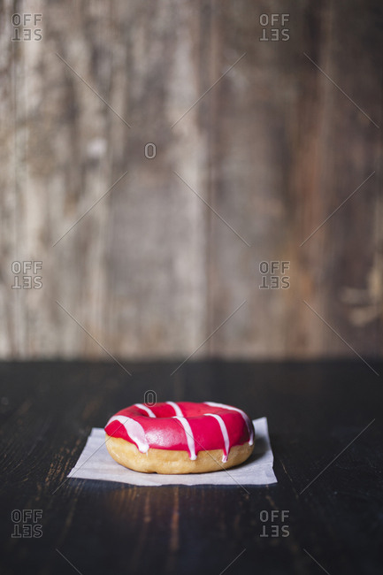 Close-up of donut with wax paper on wooden table