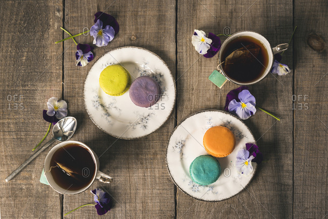 High angle view of colorful macaroons with tea and flowers served on wooden table