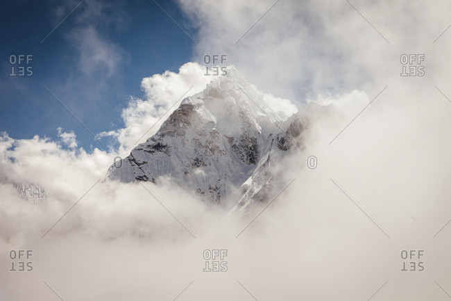 Scenic view of snowcapped mountain covered with cloudy sky during sunny day