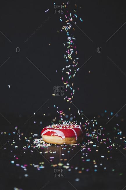 Sprinkles sprinkling on donut at wooden table against black background