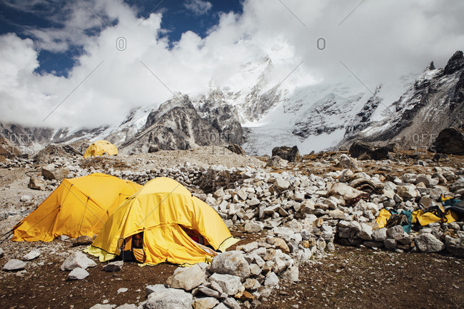 Tents on mountain against cloudy sky during sunny day