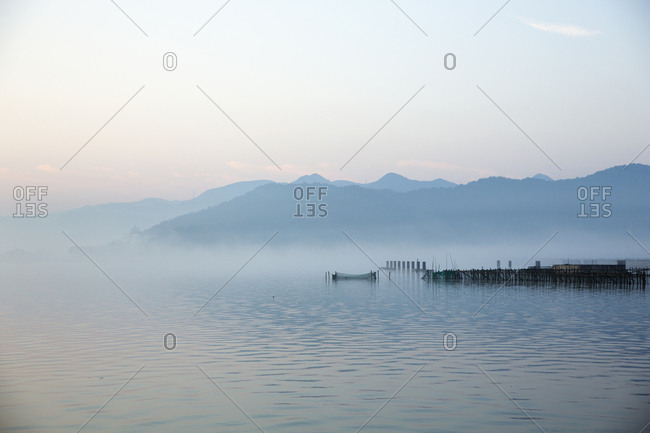 Tranquil scene of lake by mountains against sky during sunset