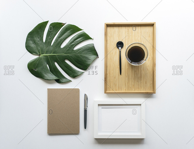Overhead view of coffee in wooden tray with monstera leaf and picture frame by office supplies arranged on white background