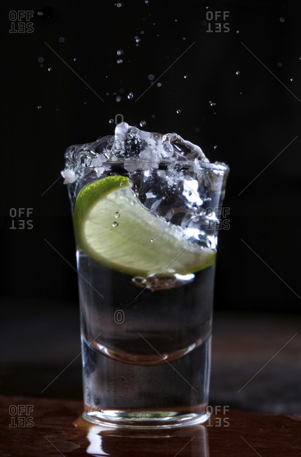 Close-up of lime slice in tequila on wooden table against black background