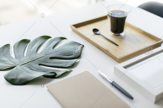 High angle view of coffee in wooden tray with monstera leaf and picture frame by office supplies arranged on table