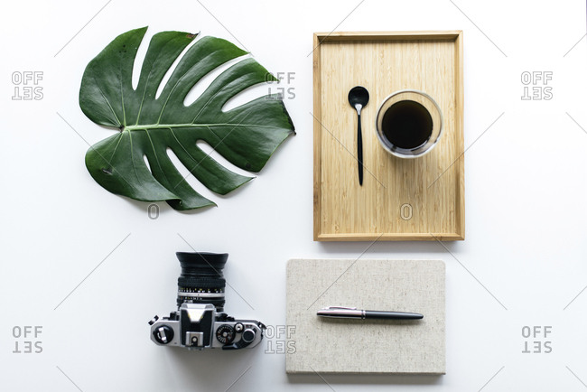 Overhead view of coffee in wooden tray with monstera leaf and camera by office supplies arranged on white background