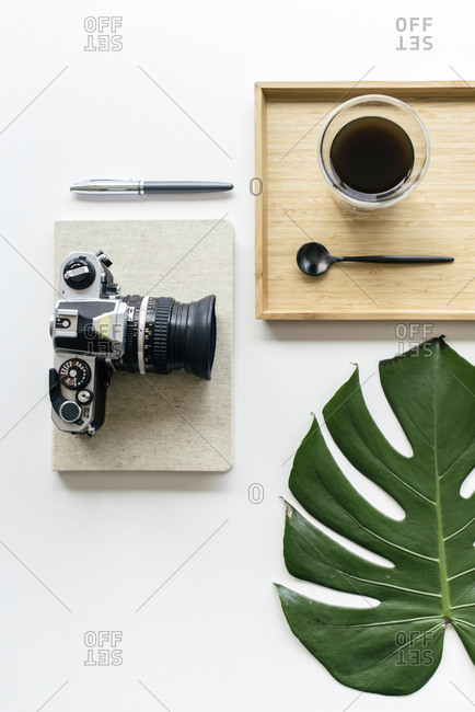 Overhead view of coffee in wooden tray with camera and office supplies by monstera leaf arranged on white background