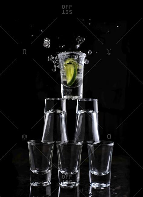 Close-up of shot glasses arranged against black background
