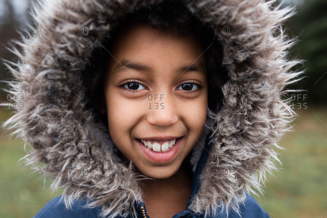 Portrait of a young girl wearing jacket with furry hood