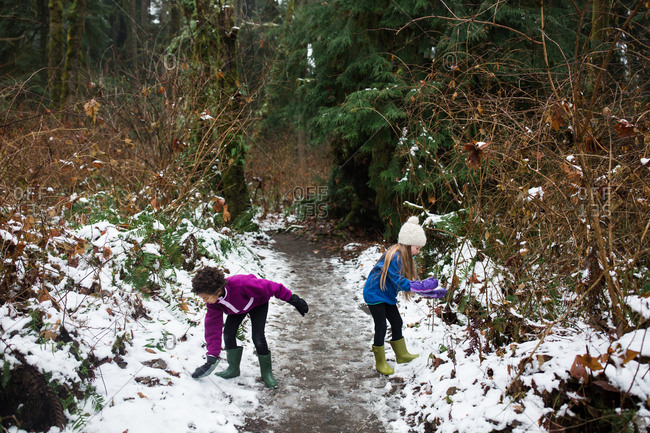 Two girls playing on snowy path