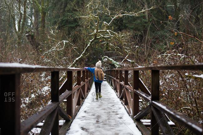 Young girl walking across snow covered bridge