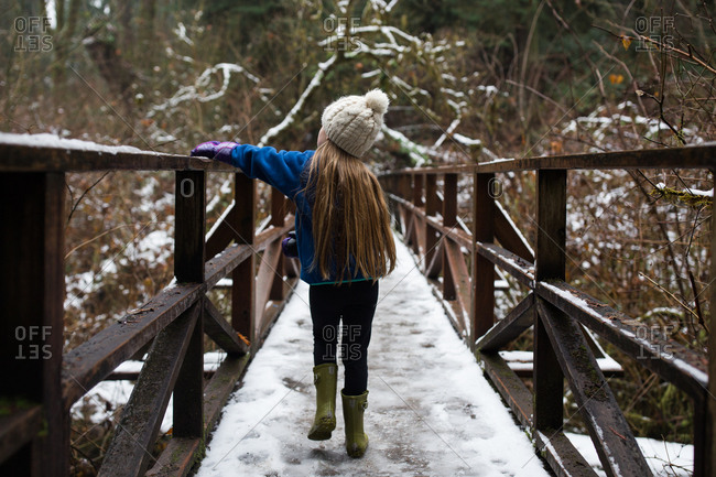 Young blonde girl walking across snow covered bridge