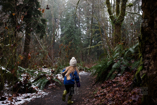 Young blonde girl hiking in forest in winter