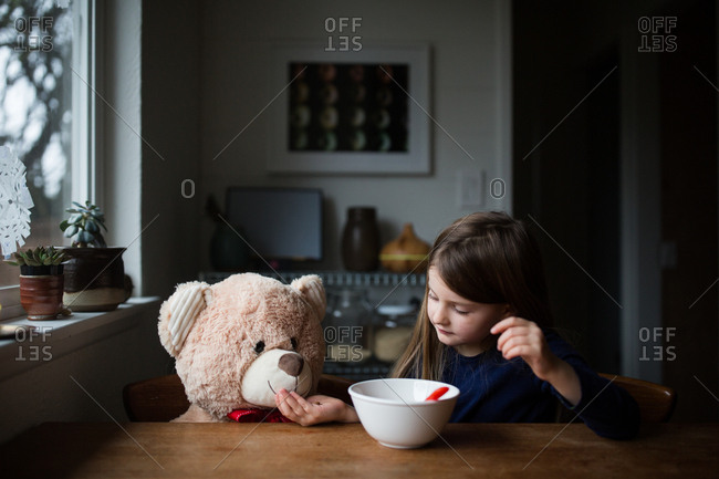 Young girl feeding teddy bear