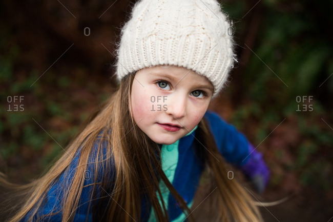 Portrait of a young blonde girl outdoors wearing knit hat