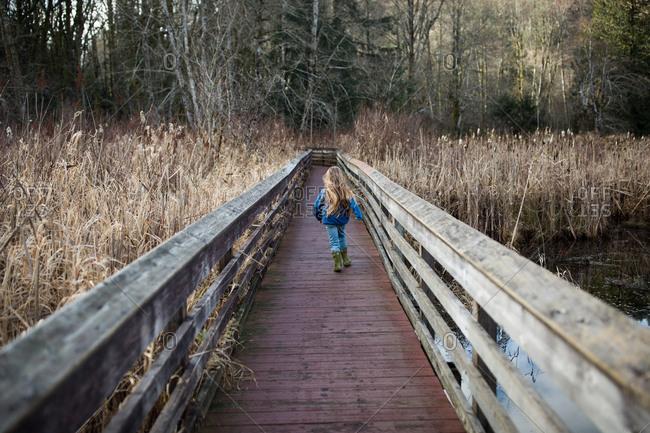 Young blonde girl running across rural bridge