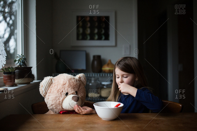 Young girl sharing snack with her teddy bear