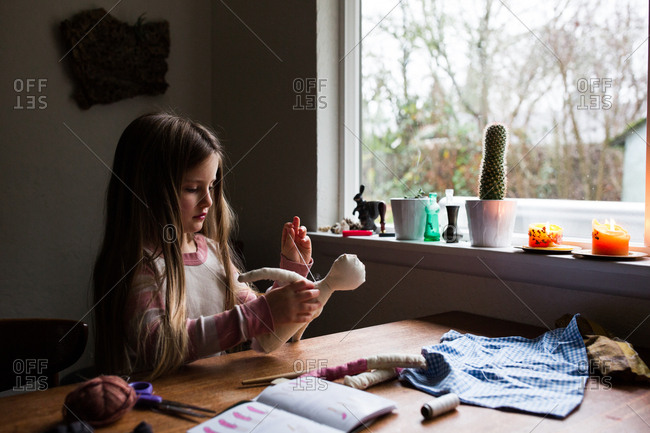 Young girl sewing a handmade doll
