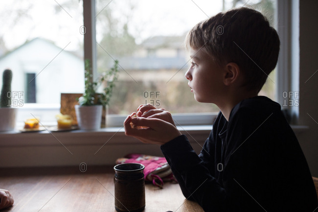 Boy drinking cup of hot cocoa and looking out window