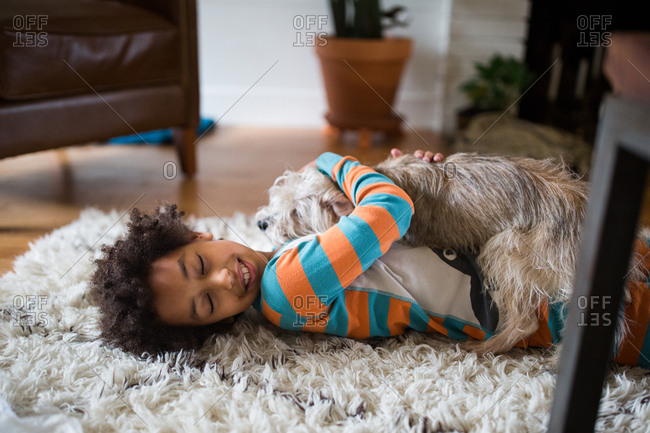Young girl cuddling on floor with furry dog