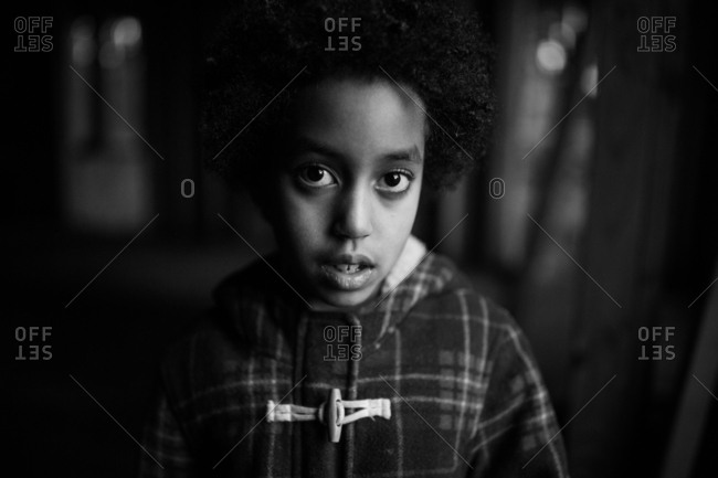 Portrait of a young girl wearing plaid jacket in black and white