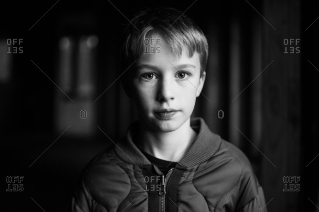 Portrait of a young boy wearing jacket in black and white