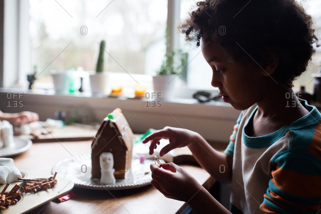 Young girl building a gingerbread house