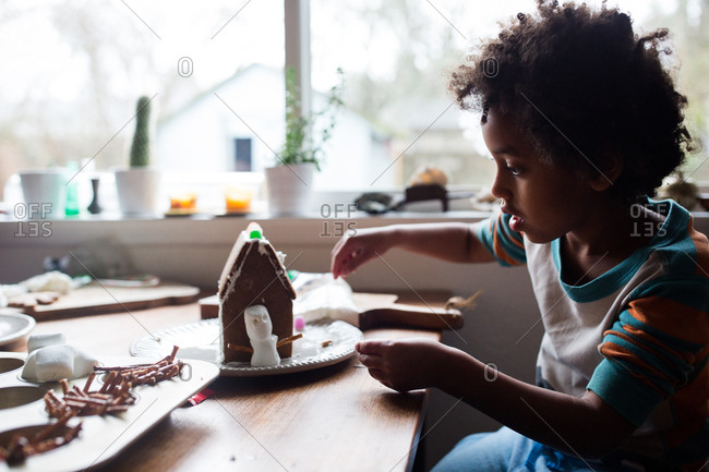 Young girl building a gingerbread house with a snowman