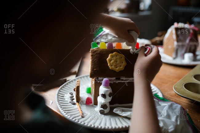 Child putting candy on a gingerbread house