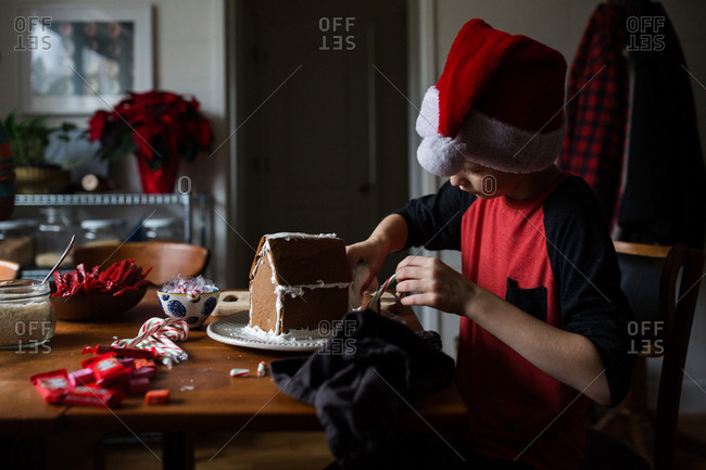 Boy wearing Santa hat and building a gingerbread house