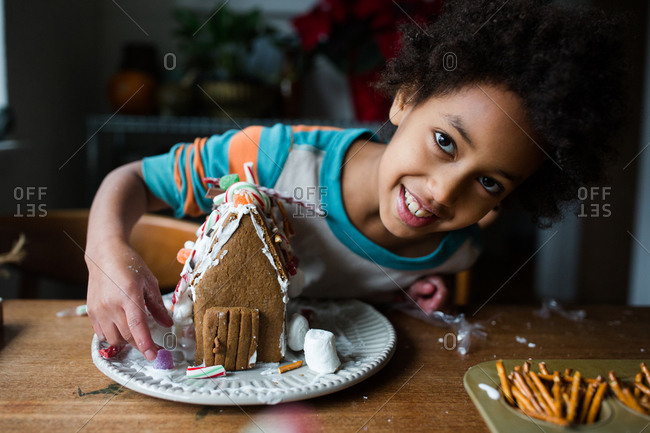 Happy girl building a gingerbread house