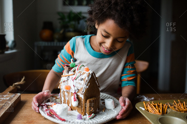 Happy girl making a gingerbread house