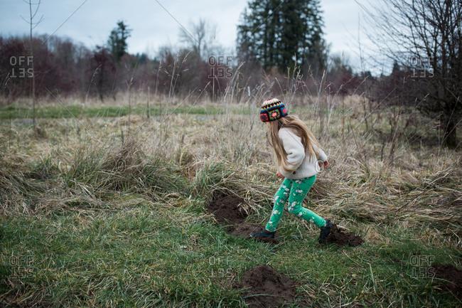 Blonde girl hiking in muddy field