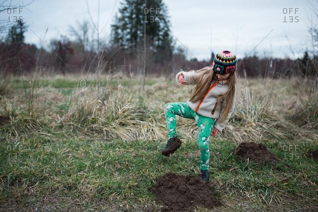 Blonde girl walking in muddy field