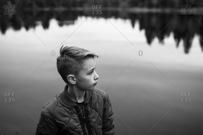 Portrait of a young boy standing by lake