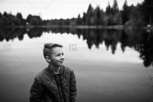 Portrait of a happy boy standing by lake
