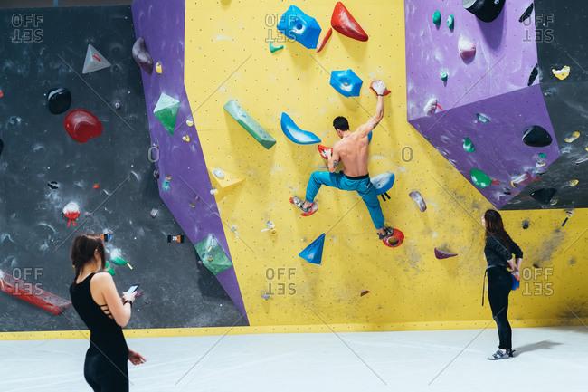 Young man climbing an indoor rock wall