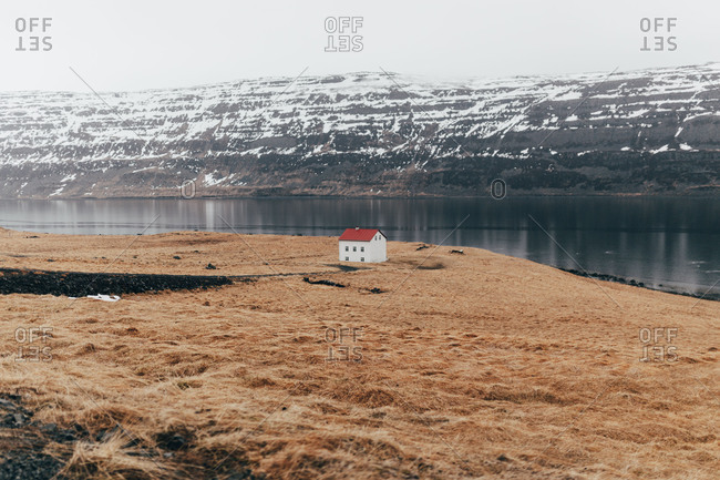 View of small remote house on terrain of lake coastline with snowy rocky hills on background, Iceland.