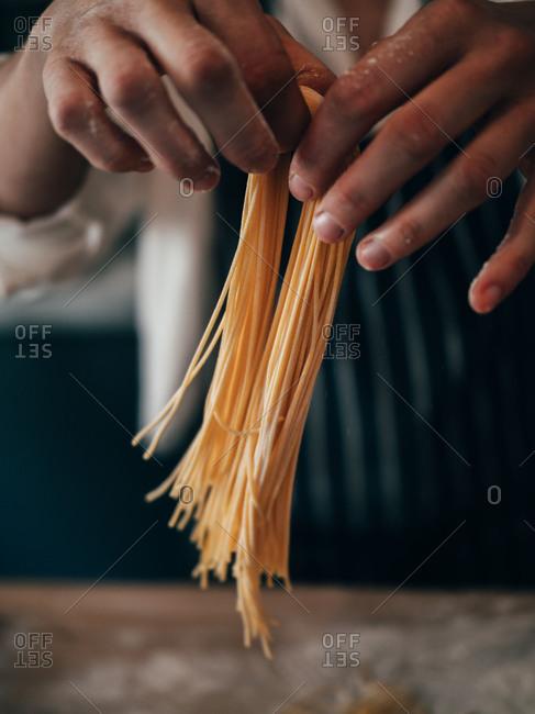 Unrecognizable cook making spaghetti