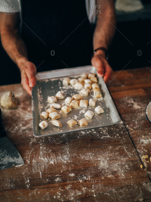 Crop person with dough pieces on pan