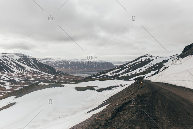 Landscape of calm road running through snowy highlands with lake on background in Iceland.