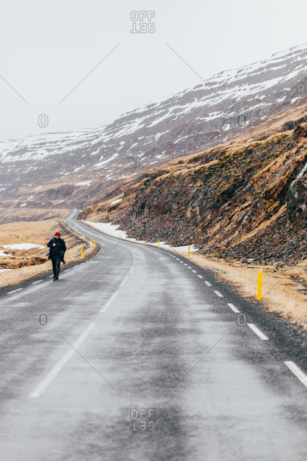 Person with backpack walking alone on long roadway below rocky mountains in cold Iceland.