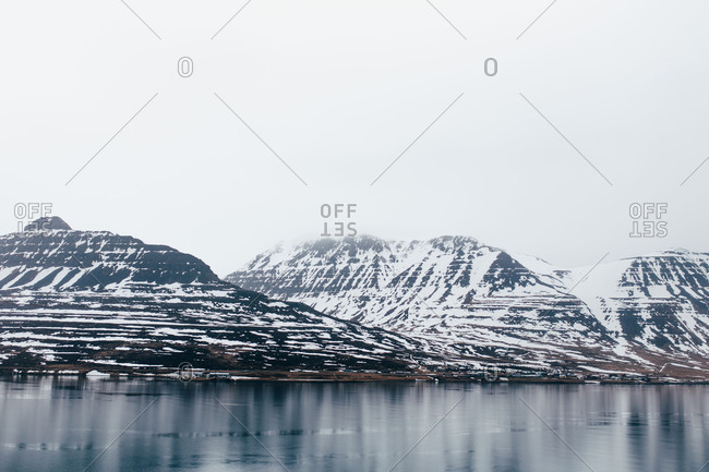 Landscape of calm cold lake water flowing slowly below rocky mountains with snow in fog, Iceland.