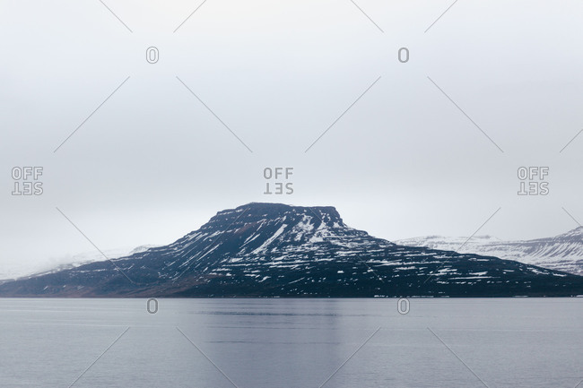 Picturesque landscape of Iceland with rocky slightly snowy mountains above calm water of lake in gloomy day.
