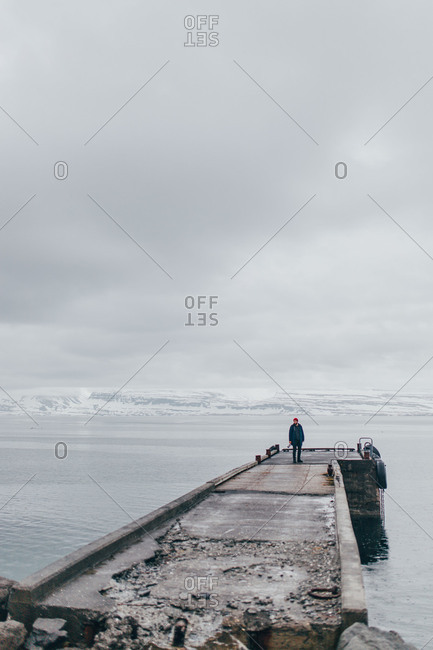 Man standing on wet stone pier in dark sea with gloomy clouds above, Iceland.